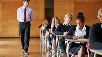 Young students sitting for exams with teacher invigilating