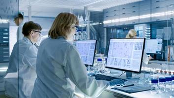 Scientists Working on their Computers In Big Modern Laboratory