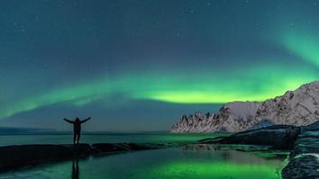 Man watching the northern lights, Aurora Borealis