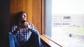 Upset student looking through window in university