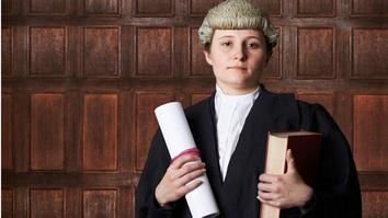 Female Lawyer In Court Holding Brief And Book