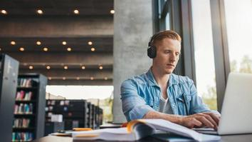 Young male student with headphones studying on the laptop