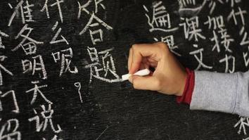 Girl writing Chinese characters on a blackboard