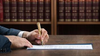 Lawyer writing on legal documents at desk in courtroom