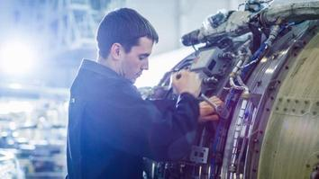 Aircraft Maintenance Mechanic Inspecting and Working on Airplane Jet Engine