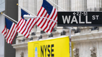 Road sign saying 'Wall St' with three USA flags behind