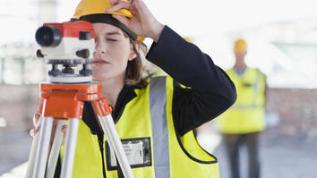 Construction student using equipment to survey
