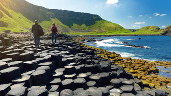 People walking on the Giants Causeway, on an area of hexagonal basalt stones, by green hills, blue skies and blue sea