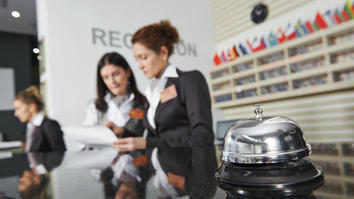 Three workers at hotel reception with bell on desk