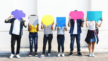 Six people holding up colourful placards that look like speech bubbles
