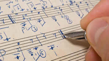 Person writing music notations onto manuscript paper