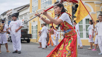 Person dancing in parade in front of yellow building and several people in white clothes