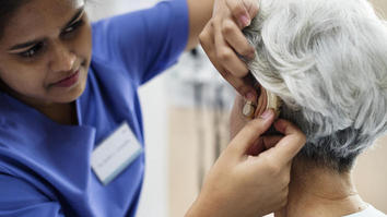Nurse fitting and elderly person with a hearing aid